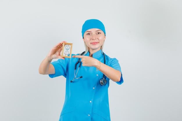 Vrouwelijke arts wijzende vinger op zandloper in blauw uniform en op zoek vrolijk.