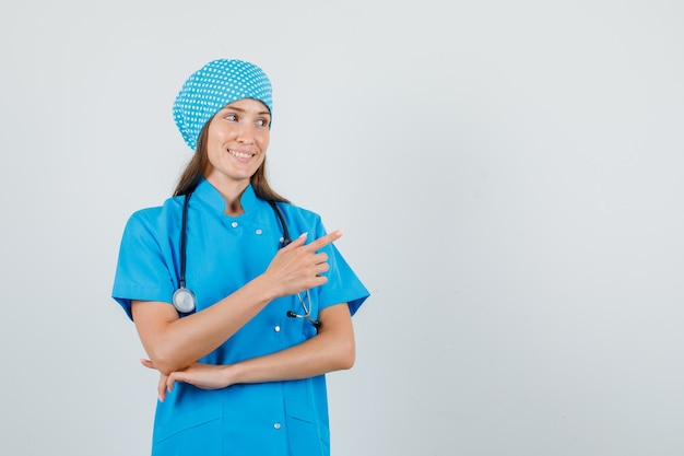 Vrouwelijke arts wijzende vinger weg in blauw uniform en op zoek vrolijk. vooraanzicht.