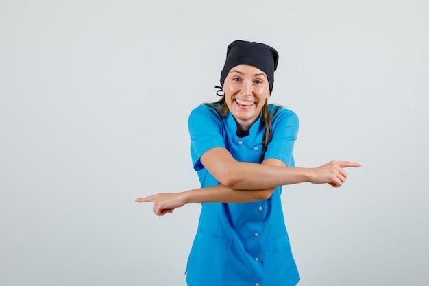 Vrouwelijke arts wijzende vingers weg en lachend in uniform