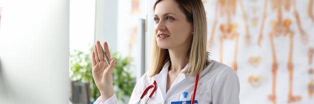 Vrouwelijke arts zit aan tafel en zwaait naar het computerscherm