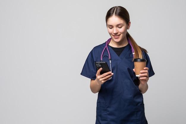 Vrouwelijke arts zit met mobiele telefoon en drinkt koffie op wit wordt geïsoleerd