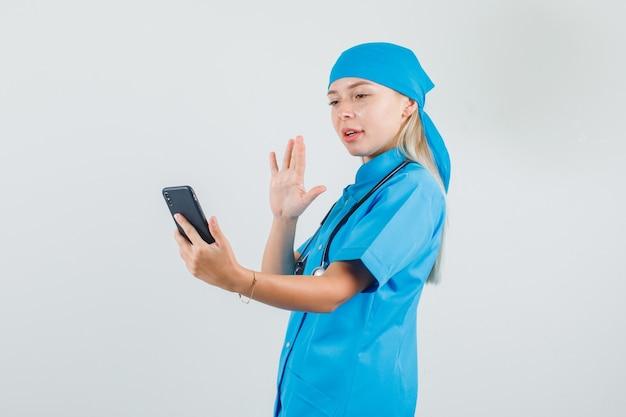 Vrouwelijke arts zwaaiende hand op videocall in blauw uniform en op zoek positief
