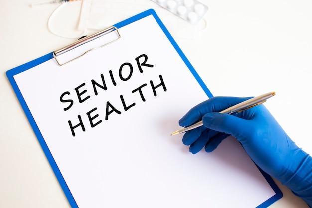 Vrouwelijke artsen hand in een medische handschoen maakt een inscriptie senior gezondheid