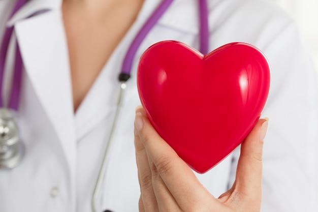 Vrouwelijke artsen handen met rood hart voor haar borst. doctor's hand close-up. medische hulp, profylaxe of verzekeringsconcept.