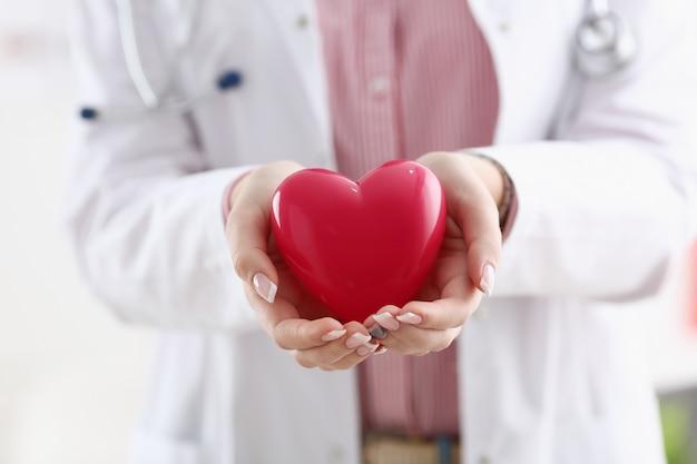 Vrouwelijke artsengreep in wapens en behandel rode stuk speelgoed hartclose-up. cardio-therapeutist student onderwijs cpr 911 leven redden arts make cardiale fysieke hartslagmaat aritmie levensstijl