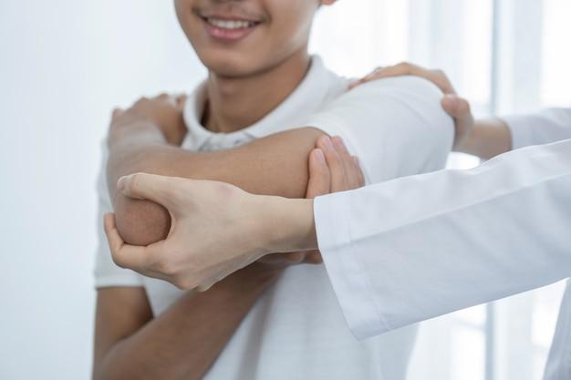 Vrouwelijke artsenhand die fysiotherapie doet door de schouder van een mannelijke patiënt uit te breiden.