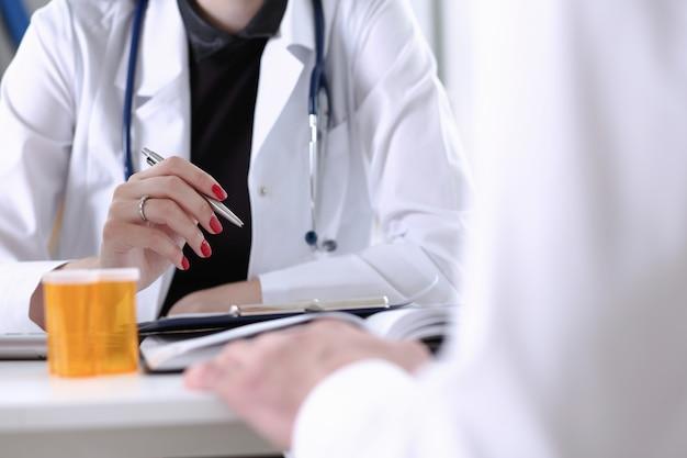 Vrouwelijke artsenhand die zilveren pen houden die geduldig document vullen
