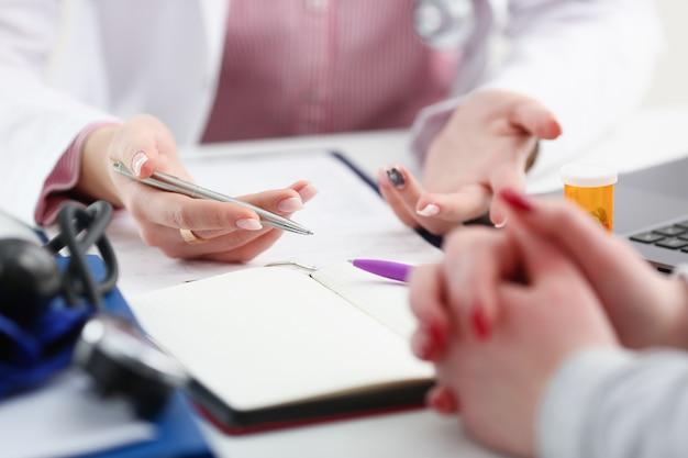 Vrouwelijke artsenhand die zilveren pen houden