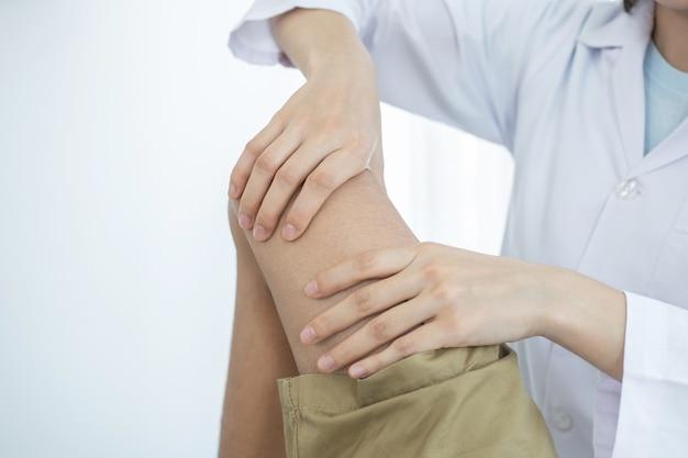 Vrouwelijke artsenhanden die fysiotherapie doen door het been en de knie van een mannelijke patiënt uit te breiden.