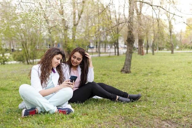 Vrouwelijke artsenstudent in openlucht met telefoon. medische achtergrond