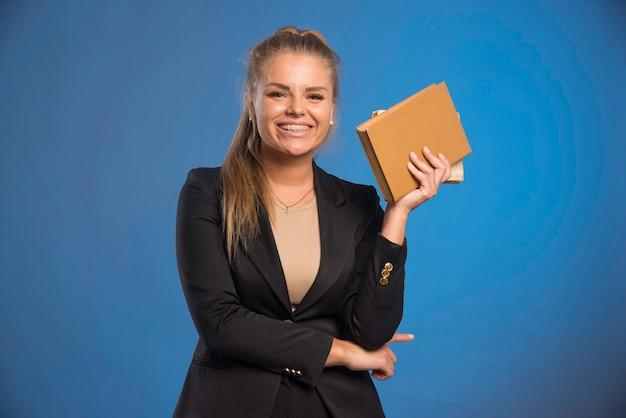 Vrouwelijke assistent die een notitieboekje met leren omslag vasthoudt en ziet er positief uit.