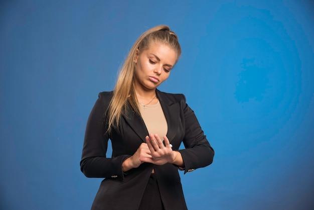 Vrouwelijke assistent kijkt naar haar hand en kijkt twijfelachtig.
