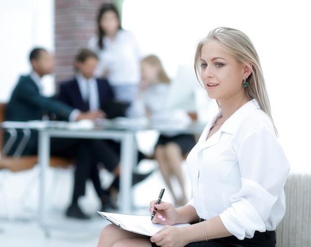 Vrouwelijke assistent met de notulen van de vergadering op de achtergrond van het kantoor
