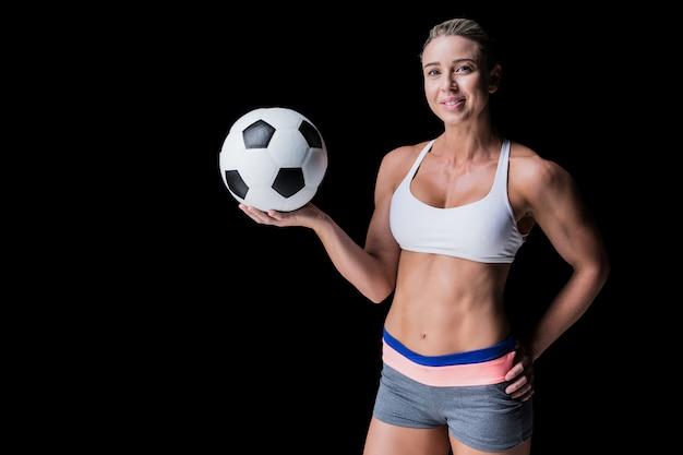 Vrouwelijke atleet die een voetbalbal op zwarte houdt