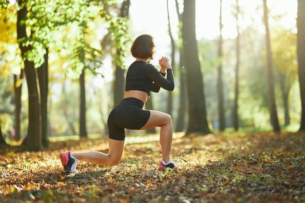 Vrouwelijke atleet die hurkzitoefeningen doet bij stadspark