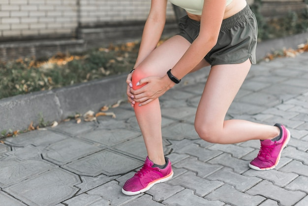Vrouwelijke atleet die pijn in knie heeft