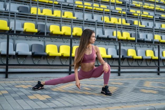 Vrouwelijke atleet doen rekoefeningen ochtend stadium. concept van sport voor het gezondheidsleven