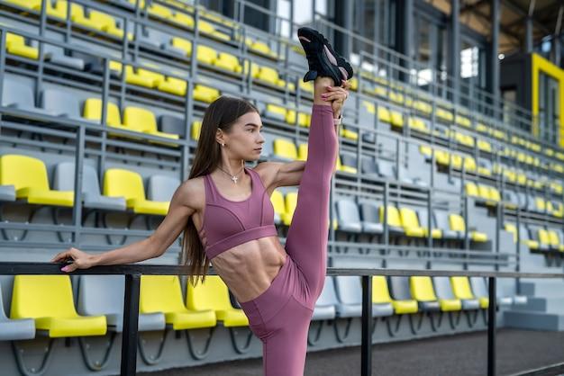Vrouwelijke atleet doen rekoefeningen ochtend stadium