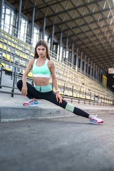 Vrouwelijke atleet doet rekoefeningen ochtend in het stadion. concept van sport voor gezond leven