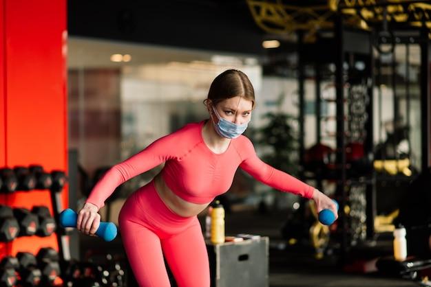 Vrouwelijke atleet fitnesstrainer dragen witte medische beschermend masker doen oefeningen met halter, uitnodigen om fitnessles te doen in lege sportschool.