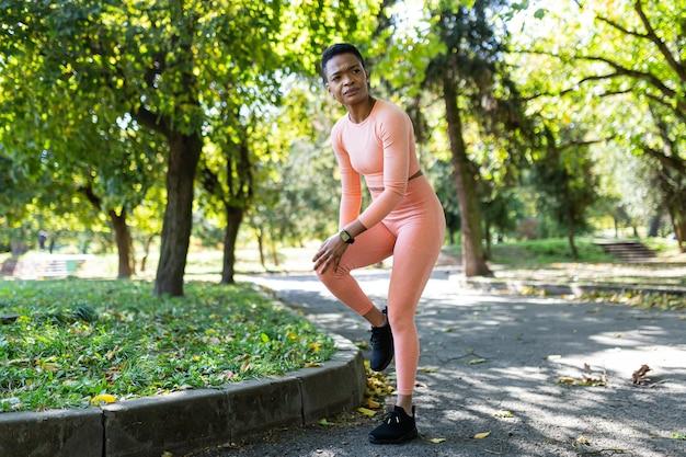 Vrouwelijke atleet heeft ernstige pijn in de benen na ochtendjoggen en fitness, afro-amerikaanse vrouw in herfstpark in de ochtend