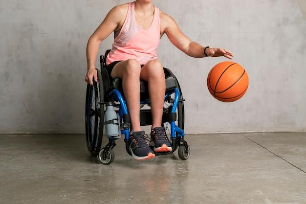 Vrouwelijke atleet in een rolstoel die een bal dribbelt
