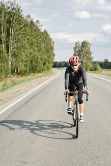 Vrouwelijke atleet in helm op weg fietstocht in prachtige natuur