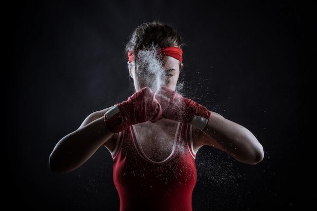 Vrouwelijke atleet in rode boksbandages en sportkleding, vooraanzicht. vechtsport concept