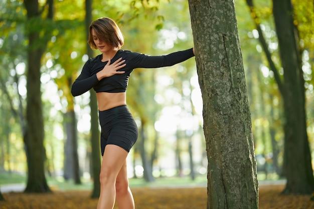 Vrouwelijke atleet in sportkleding armen buitenshuis uitrekken