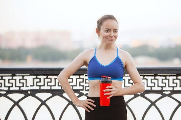 Vrouwelijke atleet met een glas sportvoeding in opleiding op een stadsstraat in de zomer.