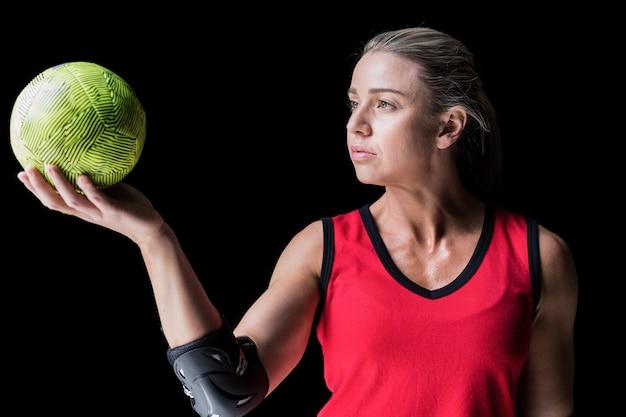 Vrouwelijke atleet met elleboogstootkussen die handbal op zwarte houden