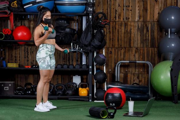 Vrouwelijke atleet met gewichten die online lesgeeft met een computer die een masker draagt voor het nieuwe normaal