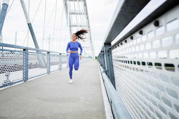 Vrouwelijke atleet met sterk lichaam en benen loopt over de brug en training
