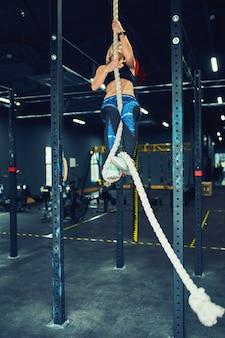 Vrouwelijke atleet of sportman klimtouw op donkere sportschool.