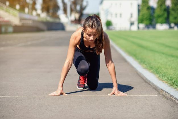 Vrouwelijke atleet op de startlijn van een stadionspoor, voorbereiding voor een run
