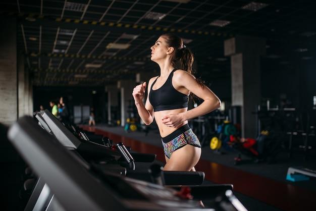 Vrouwelijke atleet op een loopband in sport sportschool. jonge vrouw in fitnessclub