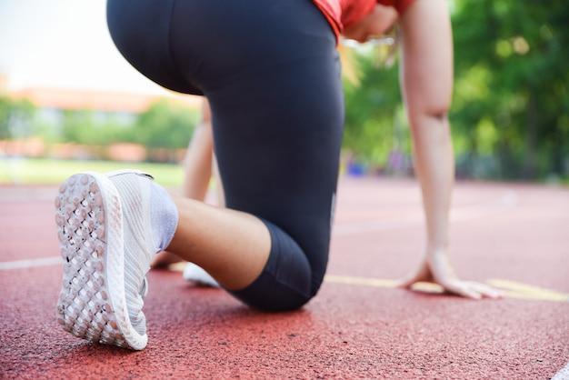 Vrouwelijke atleet op startblokken die voor looppas bij stadionspoor voorbereidingen treffen.