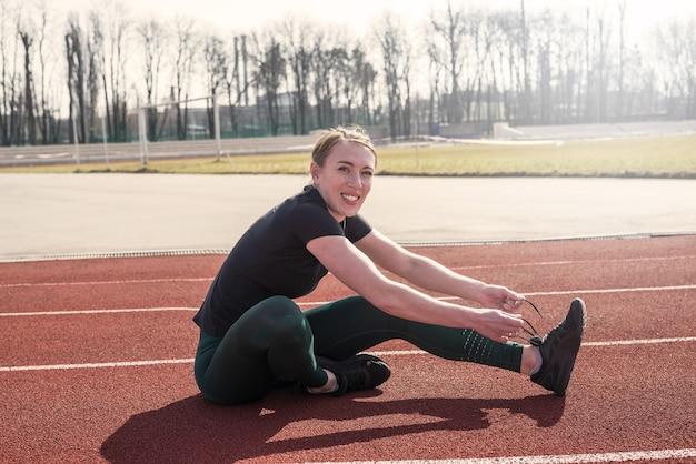 Vrouwelijke atleet veter haar sneakers op de atletiekbaan van een stadion. gezonde levensstijl.