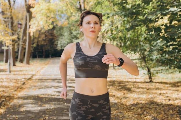 Vrouwelijke atleet vrouw runner dragen draadloze koptelefoon luisteren naar muziek op slimme telefoon