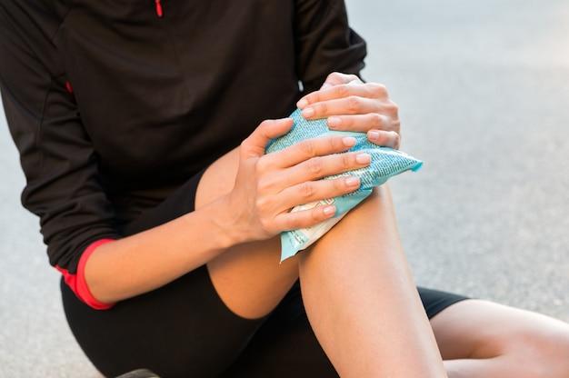 Vrouwelijke atleet zittend op de grond en behandeling voor kniepijn