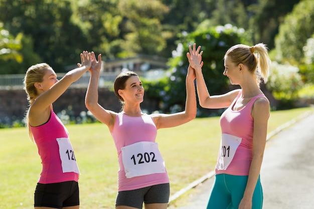 Vrouwelijke atleten die high five aan elkaar geven