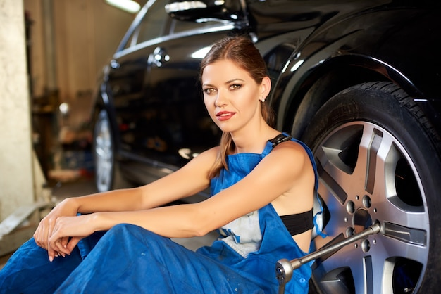 Vrouwelijke automonteur repareert auto in de garage