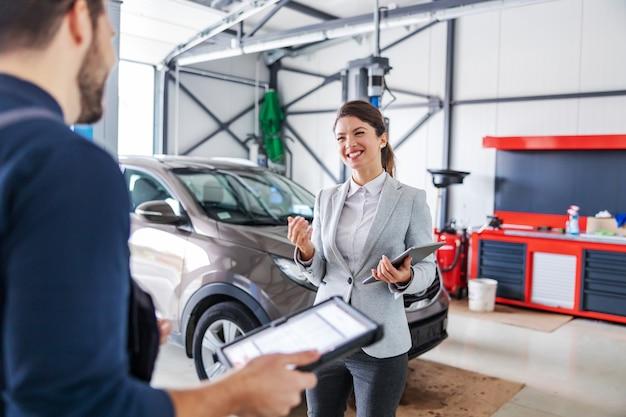 Vrouwelijke autoverkoper permanent in garage van autosalon en praten met een monteur over het repareren van de auto.