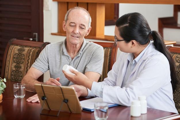 Vrouwelijke aziatische arts die geneeskunde toont aan kaukasische patiënt tijdens huisbezoek