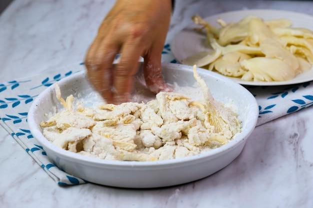 Vrouwelijke aziatische handgecoate oesterzwam met bloem, proces maken krokant gebakken oesterzwam of jamur krispi. oesterzwam bedekt met gekruide bloem en depp fried. geselecteerde focus