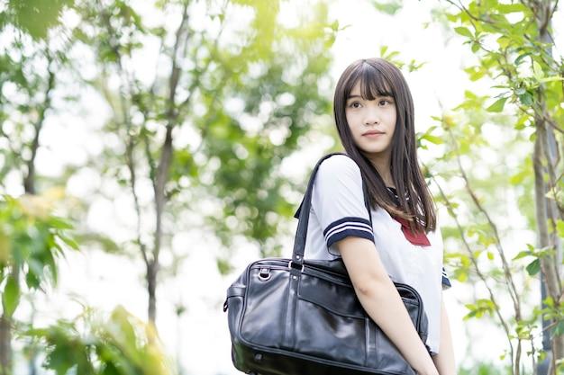 Vrouwelijke aziatische middelbare schoolstudent met een rustige blik buitenshuis