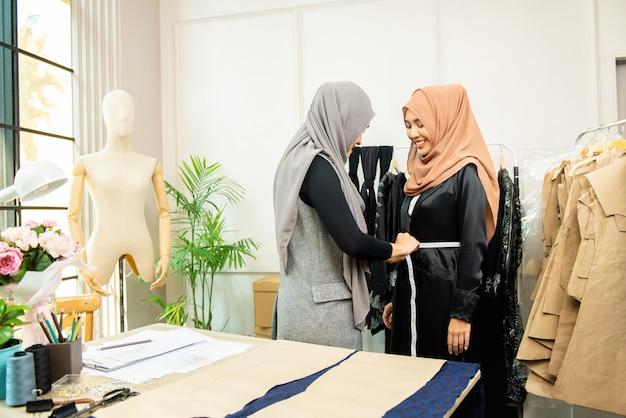 Vrouwelijke aziatische moslimontwerper die taille van klant meten