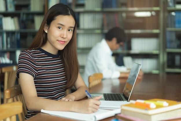 Vrouwelijke aziatische student die en boek in bibliotheek bestudeert leest