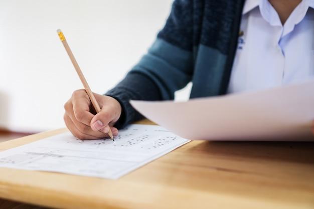 Vrouwelijke aziatische studentenhanden die examens nemen, die potlood schrijven die op optische vorm in onderzoeksruimte