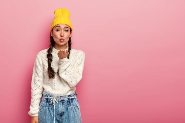 Vrouwelijke aziatische vrouw vouwt lippen en stuurt luchtkus